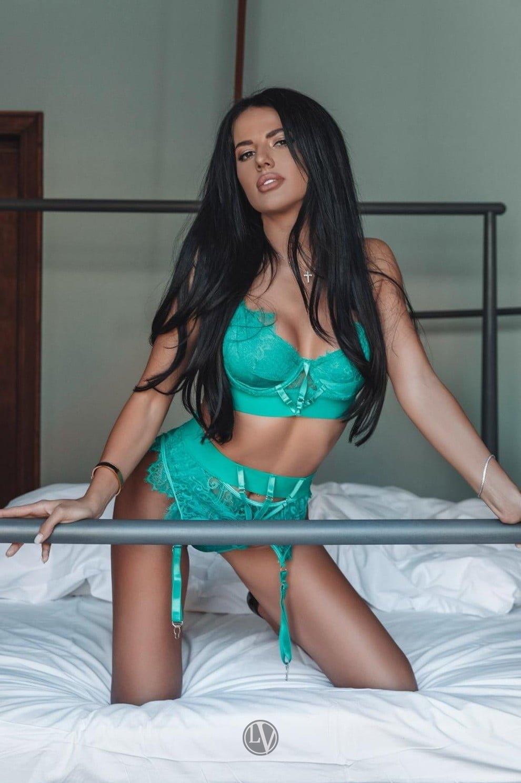 Escort Harper posing on the bed in her green underwear