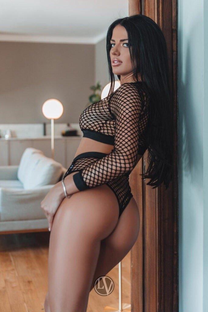 Harper standing in the doorway in her black fishnet top and knickers