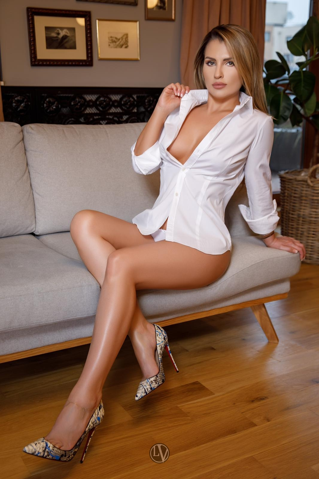 Escort June sitting on a grey sofa in a shirt and high heels
