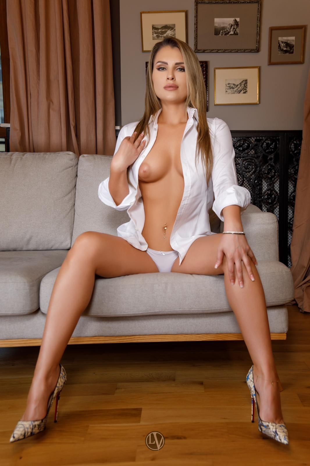 June sitting on the sofa in a white shirt and heels