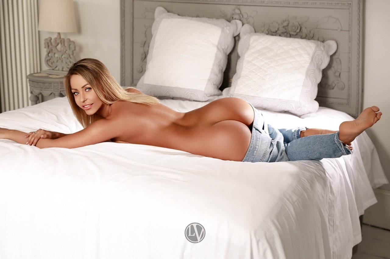 Escort Zoe lying on the bed in her jeans