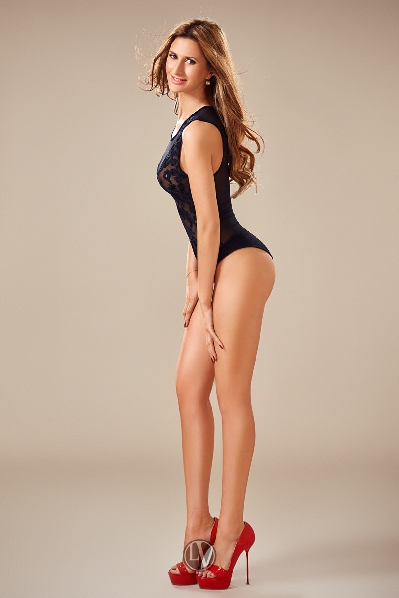 Escort Annabelle in a black swimsuit and high heels
