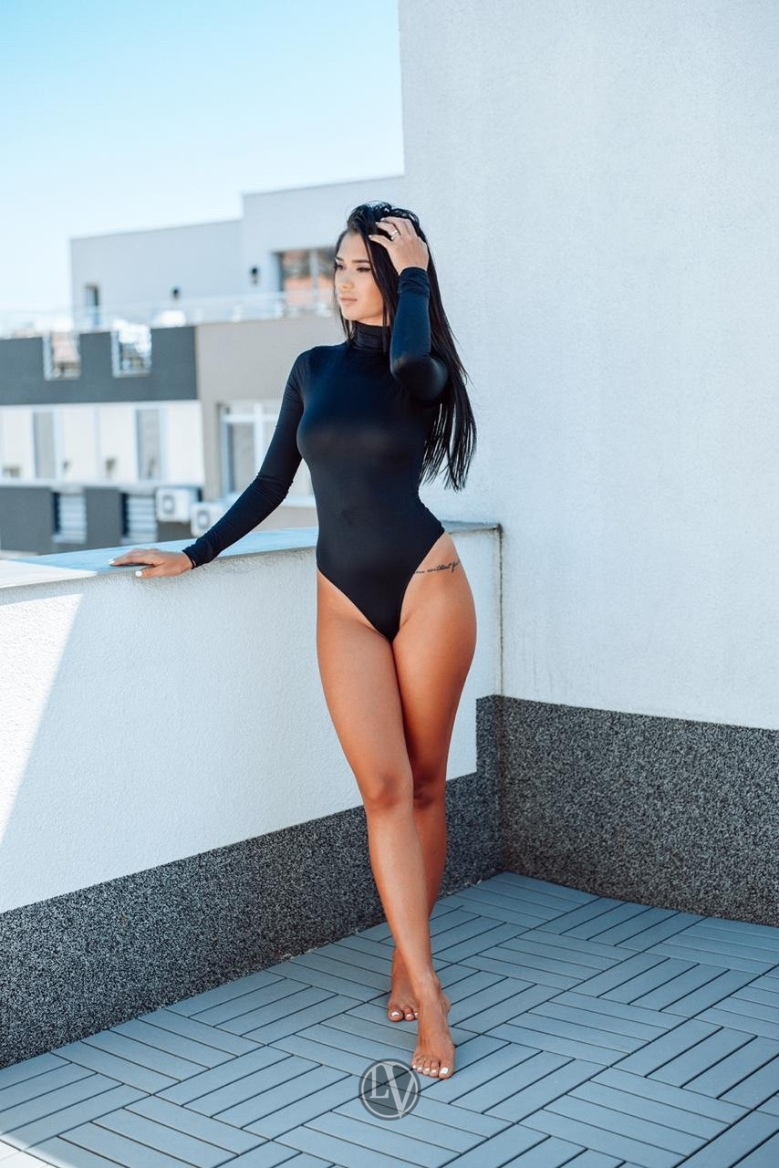 Model Carla standing by the wall in a black bodysuit