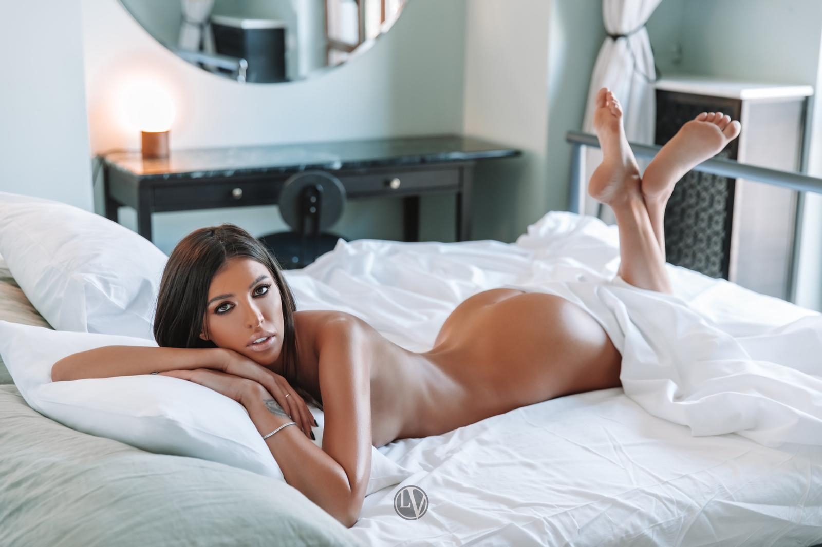 Ivanka lying on the bed with a white sheet over her
