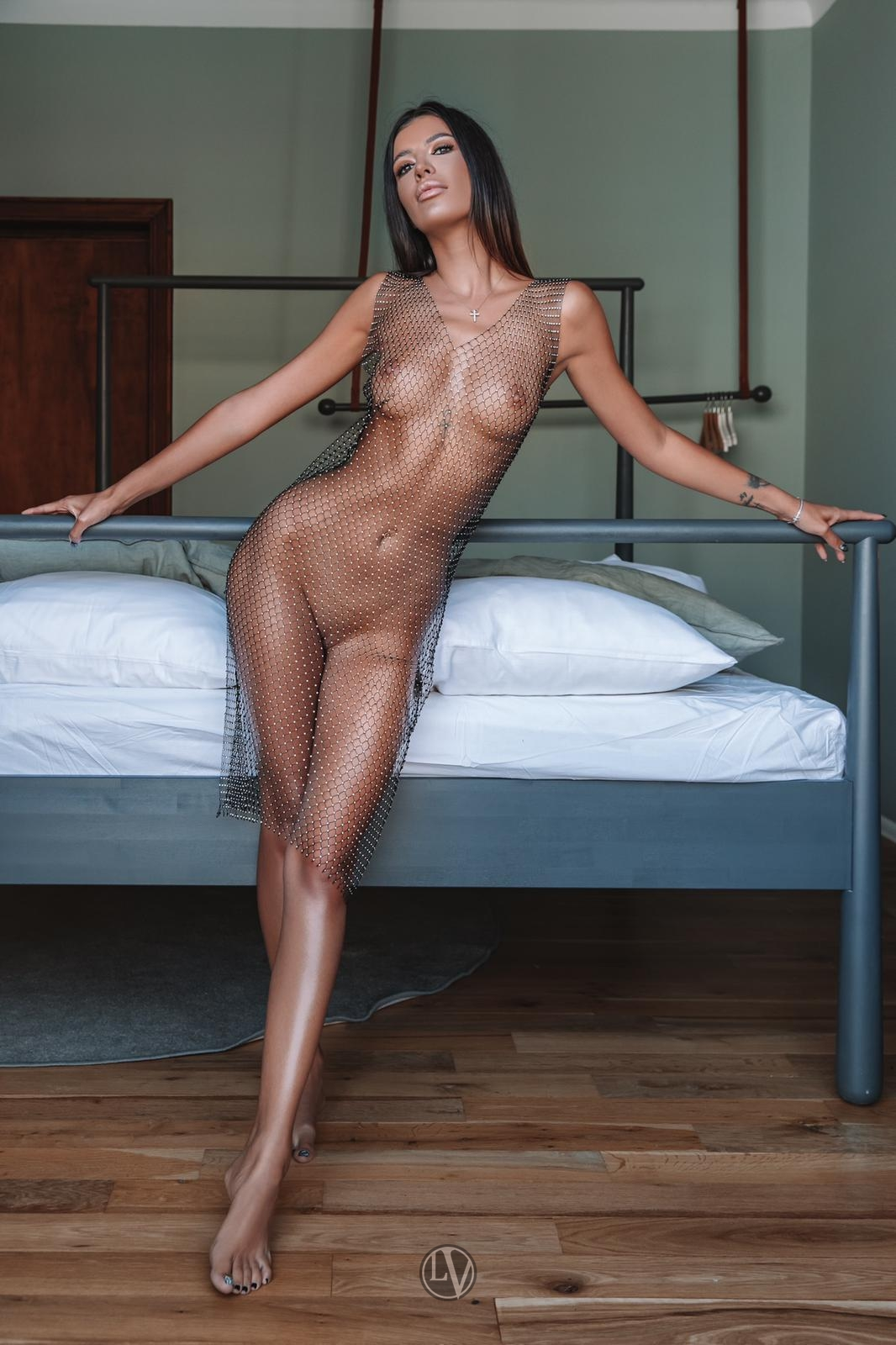 London callgirl Ivanka standing by the bed in a see-through dress
