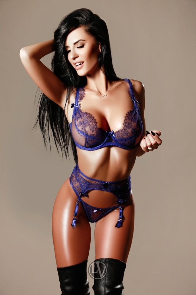 Escort Sapphire in her purple lingerie and boots.
