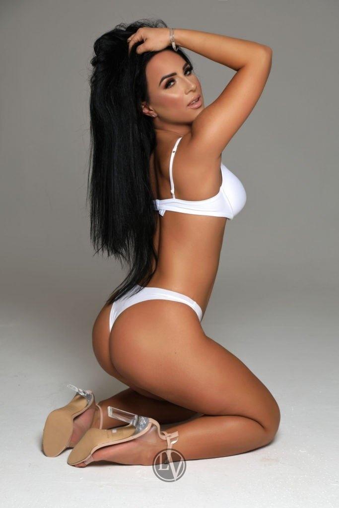 Top escort Harlie sitting on the floor in an erotic pose