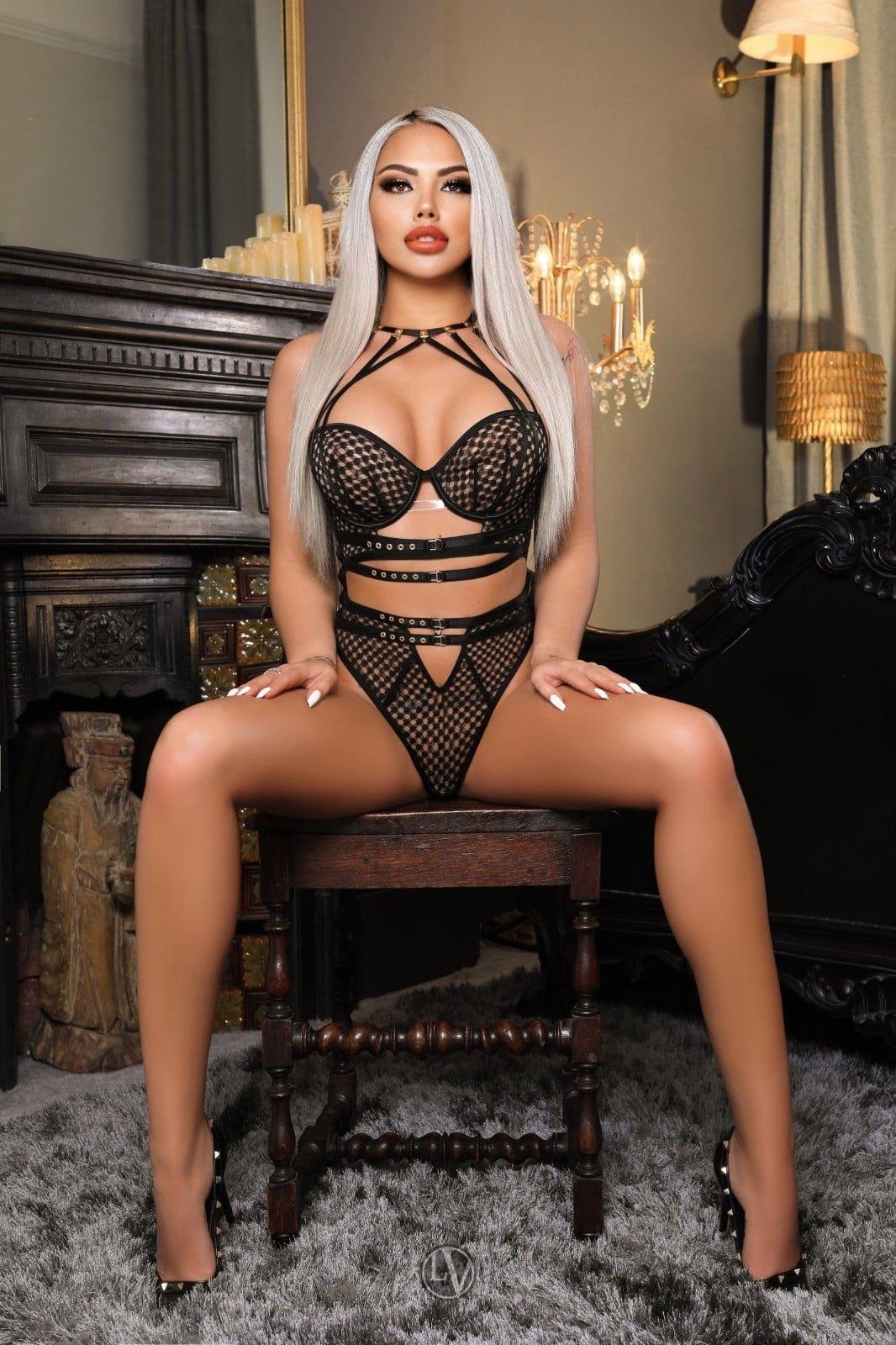 Blonde callgirl Amira sitting on a chair in her black underwear