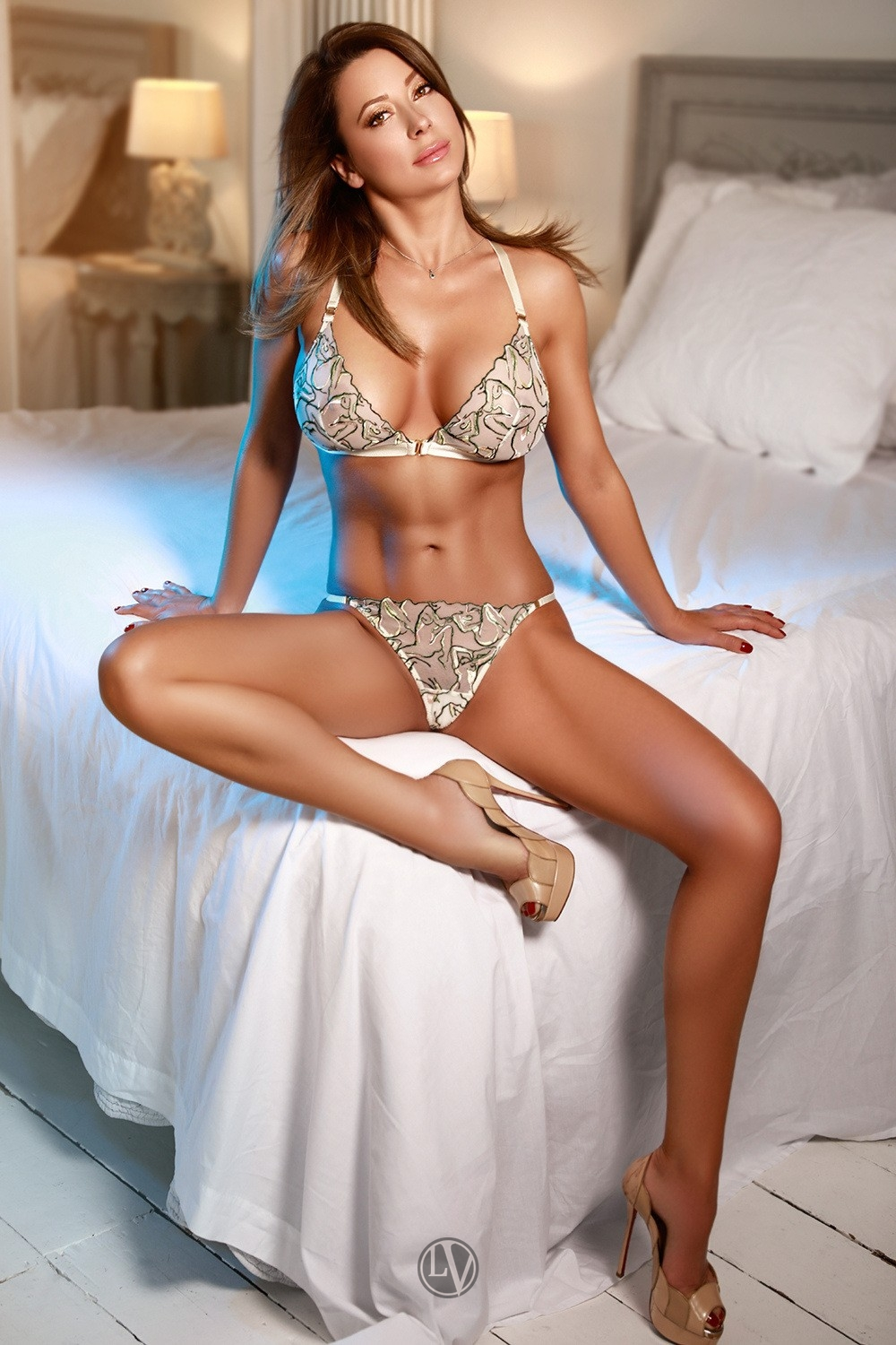 London escort Grace sitting on the bed in her underwear and heels